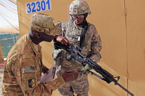 First Sgt. Irwin Whittington of the 584th Ordnance Maintenance Company, 17th Combat Sustainment Support Battalion, inspects Sgt. Reginald Miniweather's weapon during the battalion's Warrior of the Month Board. Miniweather is a Motor Transport Operator with the 109th Transportation Company, 17th Combat Sustainment Support Battalion. (Photo by Sgt Jesse McCullough)