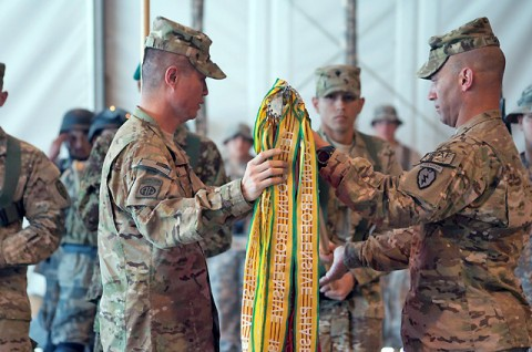 U.S. Army Col. Richard C. Kim, commander of Task Force Bronco, 3rd Brigade Combat Team, 25th Infantry Division, from Honolulu, and U.S. Army Command Sgt. Maj. Andrew J. Spano, command sergeant major of TF Bronco, 3 BCT, 25th Inf. Div., from Northboro, Mass. unfurl their unit colors during the transfer of authority ceremony at Forward Operating Base Fenty, Afghanistan, May 3rd. (Photo by U.S. Army Spc. Hillary Rustine, Task Force Bronco)