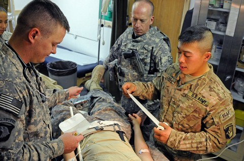 Spc. Michael Grimes and Pfc. Garry Lim, medics with the 101st Special Troops Battalion, 101st Sustainment Brigade, care for a staged injured Soldier during a mass casualty exercise, June 8th, as Col. (Dr.) Peter Napolitano, the brigade surgeon looks on. (Photo by Spc. Michael Vanpool)