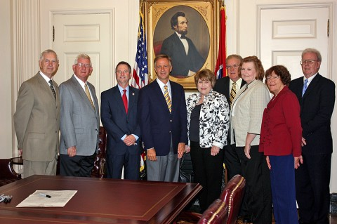Governor Bill Haslam (center) stands with State Senator Tim Barnes (third from left) and State Representative John Tidwell (left) on Wednesday, June 22nd after signing their Senate Bill 710, which increases restrictions against registered sex offenders entering public libraries. From L to R: Tidwell, Houston County mayor G.E. Clark, Barnes, Haslam, Houston County Library Director Kay French, and library board members Randall French, Susan Bell, Ann Young and Kent Bell.