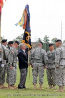 Command Sgt. Maj. James E. Musgrove Ret. presents the regimental colors to the outgoing and incoming commanders