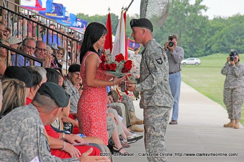 Spc. Nicholas Robinson presenting a bouquet of red roses to Col Luong's wife Kim