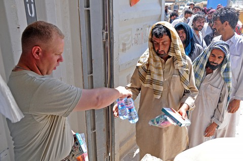 Spc. Shaun Donahue of the 584th Maintenance Company, 142nd Combat Sustainment Support Battalion, 101st Sustainment Brigade, provides an Afghan driver with bottled water and a Halal meal. The drivers will soon have a place to get cooked food and to pray and wash themselves at the soon-to-be constructed Life Support Center. (Photo by Sgt. 1st Class Peter Mayes)