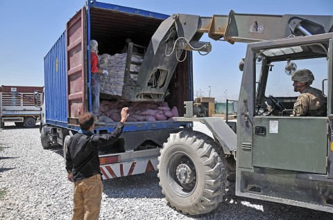Staff Sgt. William Lyons of the 584th Supply Maintenance Company, 142nd Combat Sustainment Support Battalion, 101st Sustainment Brigade, loads bags of flour into the back of a truck Bagram Humanitarian Yard. The battalion recently sent more than 600,000 pounds of supplies to a local village of Sar-E Pol, which was suffering from a drought. (Photo by Sgt. 1st Class Peter Mayes)