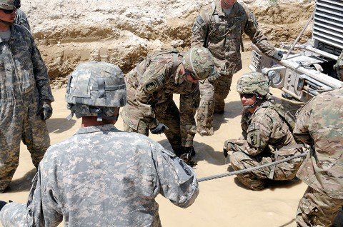 First Lt. Krystal Hertenstein, a platoon leader for the 584th Maintenance Company, 142nd Combat Sustainment Support Battalion, 101st Sustainment Brigade, helps rig a snatchbox to recover a MAX-Pro vehicle from a mire pit during the brigade's Leadership Professional Development course. (Photo by Spc. Michael Vanpool)