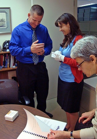 """1st Sgt. Mark Baker looks at """"Karen's Wings"""" for the first time since they were returned to Mike Low in 2002. Baker provided an oral history interview about the wings to Jenny Pachucki (center), oral historian for exhibitions, National September 11th Memorial and Museum. (Kimberly Tiscione)"""