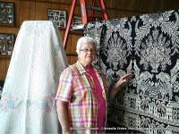 Helen Bellar showing off a woven coverlet