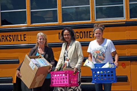 """Volunteers helping to """"Stuff the Bus"""" with much needed supplies and donations."""