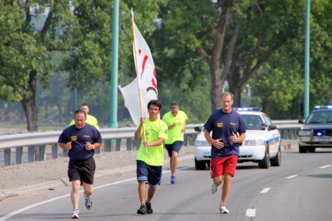 Deputy Chief Frank Gray (Left), Tyler Hodge (Center with Flag), Chief Al Ansley (Right Rear), William Smith ( Left Rear),  and Tristen Allen  (Right Rear) race down Riverside Drive with the Youth Olympic Banner.
