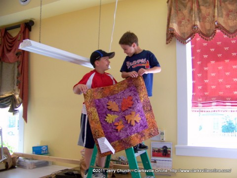 Two young boys help hang quilts as Trenton gets ready for their annual quilt show