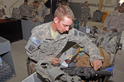 Spc. Levi White, a customs agent for the 45th Military Police Detachment, 101st Special Troops Battalion, 101st Sustainment Brigade, checks the weapon and baggage of a soldier heading home from deployment. (Photo by Sgt. 1st Class Peter Mayes)