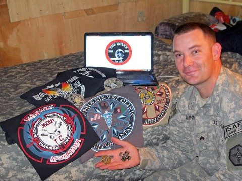 Sgt. Michael Dunn, an ammunition supply manager with the 592nd Ordnance Company, 142nd Combat Support Sustainment Battalion, 101st Sustainment Brigade, poses next to the custom T-shirts and coins he created while deployed to Afghanistan. (Courtesy Photo)