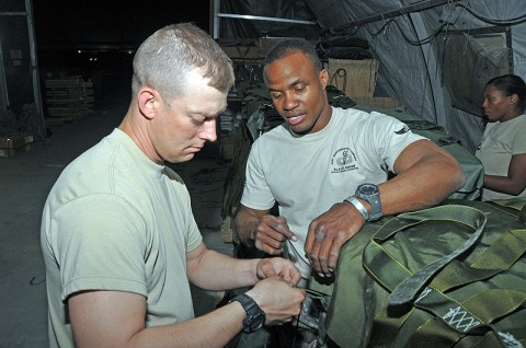 Sgt. 1st Class Narada Johnson (right), a rigger assigned to the 4/647th Quartermaster Detachment, 101st Special Troops Battalion, 101st Sustainment Brigade, instructs Staff Sgt. James Menard of the 101st Sustainment Brigade Support Operations, on how to properly rig a bundle. The Detachment worked long into the night and early morning hours preparing 60 bundles of ammunition and water for soldiers at Task Force-Currahee. (Photo by Sgt. 1st Class Peter Mayes)
