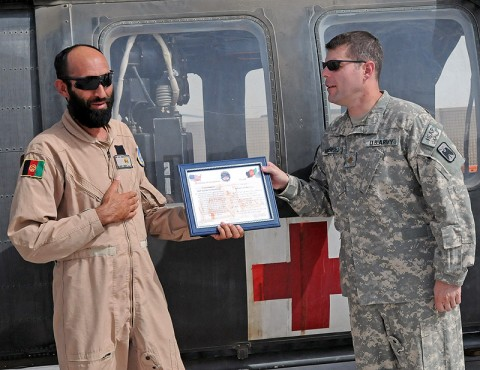 Afghan Air Force flight medic Sgt. Gulap Ahmadzia receives a certificate of completion, July 27th, from Company C, 1st Battalion, 52nd Aviation Regiment company commander Maj. Michael Mendenhall, for completion of the U.S. Army and Afghanistan Air Force medical evacuation partnership program here. Ahmadzia is the first Afghan flight medic to join Task Force Thunder's medevac crews as they move patients off of the battlefield. (Photo by Sgt. Shanika Futrell)