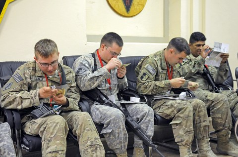 Soldiers with the 101st Finance Management Company, 101st Special Troops Battalion, 101st Sustainment Brigade, use magnifying glasses and ultraviolet lights to identify fake money during a counterfeit currency training. (Photo by Spc. Michael Vanpool)