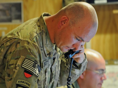 Staff Sgt. Joshua DeWitt, the fire support officer for Task Force Wings, calls to establish a restricted operating zone as he verifies grid coordinates for support from a mortar team at Forward Operating Base Wolverine July 27th. (Photo by Sgt. 1st Class Stephanie Carl)