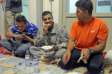 First Lt. Shuja Kazmi, the command group administrative officer for the 101st Sustainment Brigade, shares a meal at sunset with interpreters of the brigade and fellow Muslims at a mosque on Bagram Air Field. (Photo by Spc. Michael Vanpool)