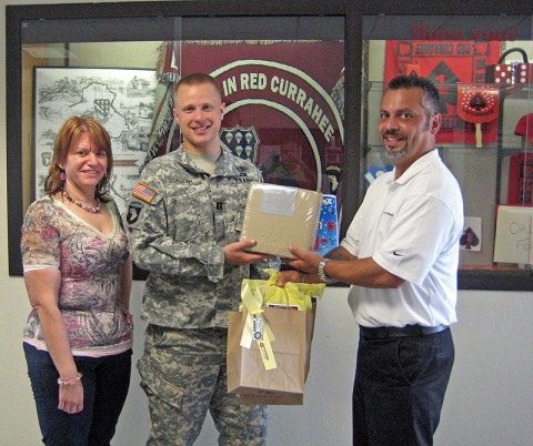 Wyatt-Johnson auto rep Willie Rosario presents sheets and a gift bag to FRG leader Tammy Phillips and Cpt. Smith, rear detachment commander for 4th Brigade Combat Team 506th Infantry Regiment.