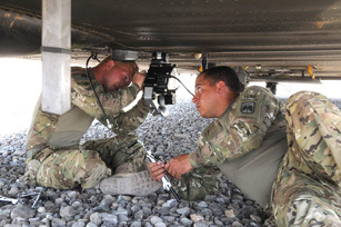 Spc. David Rydel (right) of Inver Grove Heights, MN, hands a wrench to Spc. Kenneth Jones of Nelson, MO, as they attach a part to a CH-47D Chinook helicopter here July 23rd. Both Soldiers are maintainers for Company B, 1st Battalion, 52nd Aviation Regiment, which is a new asset to Task Force Thunder. (Photo by Jennifer Andersson, 159th Combat Aviation Brigade).