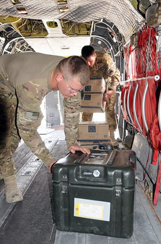 Sgt. Daniel Scott (left) of Denton, TX, and Sgt. William Rose of Ormand Beach, FL, flight engineers for Company B, 1st Battalion, 52nd Aviation Regiment, organize necessities for flights in their first week in Afghanistan July 23rd. (Photo by Jennifer Andersson, 159th Combat Aviation Brigade)