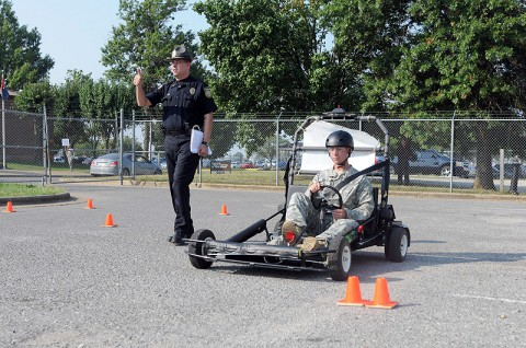 Police Lt. Raymond Lepper, a provost martial with the Directorate of Emergency Services, walks with Spc. Ian Murphy, a rifleman with Company B, 1st Battalion, 327th Infantry Regiment, 101st Airborne Division, as he gets a feel for the Simulated Impaired Driving Experience course here, Sept. 1. The SIDNE provided unique training to soldiers during Safety Stand-down Day to simulated driving under the influence while the driver was still sober. (Photo by Spc. Richard Daniels Jr.)