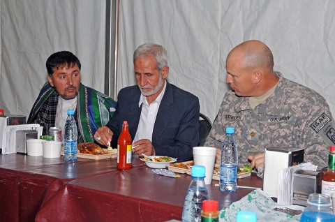 Deh Dadi District Deputy Subgovernor Mohammad Akbar Askari (center) enjoys his lunch with Maj. John Stringer (right), executive officer for the 530th Combat Sustainment Support Battalion, 101st Sustainment Brigade, at the base dining facility. The battalion commander's emergency response program team hosted Askari and other village elders while also discussing future development projects for the district. (Photo by Sgt. 1st Class Peter Mayes)