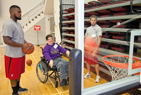 APSU students Ashlon Adams (left) and Brian Bourland play basketball with Dee during an adapted physical education class September 23rd in the Dunn Center. (Photo by Beth Liggett, APSU photographer)