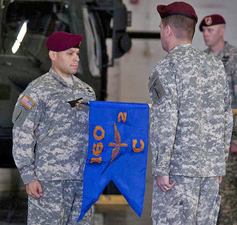 Maj. Keith Sandoval (left), commander of C Company 2nd Battalion, 160th Special Operations Aviation Regiment (Airborne), and Lt. Col. Phil Ryan, commander of 2nd Battalion 160th SOAR (A), watch as the company colors are unfurled for the first time during an activation ceremony at Fort Campbell, KY., Sept. 12th, 2011. (160th Special Operations Aviation Regiment courtesy photo)