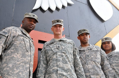 "Master Sgt. Lamar Chancellor, Command Sgt. Maj. David Thompson, Staff Sgt. Michael Simon and Sgt. 1st Class Fiona Bunn of the 101st Sustainment Brigade pose underneath the brigade's emblem at their headquarters. These non-commissioned officers were part of the ""Be All You Can Be"" generation of soldiers on active duty during the September 11th, 2001 attacks and have witnessed the Army's transformation from the Cold War to the Global War on Terrorism. (Photo by Sgt. 1st Class Peter Mayes)"