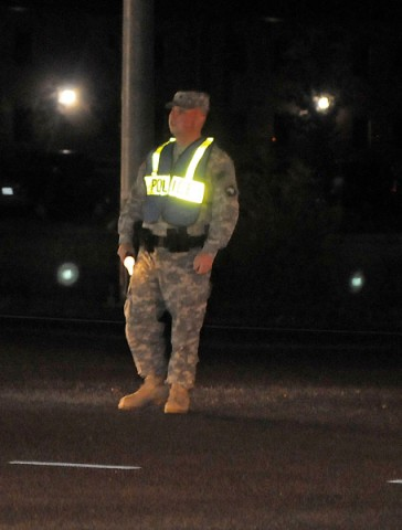 Spc. Ryan P. Carroll, a patrolman with Headquarters and Headquarters Company, 1st Special Troops Battalion, 1st Brigade Combat Team, controls traffic at his Traffic Control Point, October 17th, at the intersection of Indiana Avenue and Bastogne Street. (Photo by Sgt. Jon Heinrich)