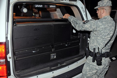 Staff Sgt. Robert J. Streit, patrol supervisor from Headquarters and Headquarters Company, 1st Special Troops Battalion, 1st Brigade Combat Team, secures the equipment lock boxes located in the back of his vehicle Oct. 17th outside the post police station during his vehicle inspection before heading out on patrol. (Photo by Sgt. Jon Heinrich)