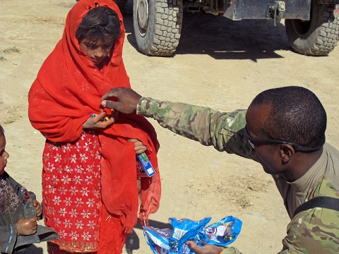 Master Sgt. Terrence Reyes, the operations NCOIC for Task Force Wings (4th Battalion, 101st Aviation Regiment) hands candy to an Afghan girl during a humanitarian visit here October 1st. TF Wings and TF 77 conducted a humanitarian assistance visit and key leader engagement at the Bolla Baba High School here.  (U.S. Army Photo by Staff Sgt. Joshua Dewitt, Task Force Wings Fire Support Officer /released)