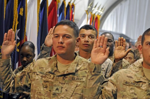 Spc. Francisco Javier Fuentes (background), a command group driver for the 101st Sustainment Brigade, joins the other soldiers and recited the oath to allegiance to become a U.S. citizen at the Joint Sustainment Command - Afghanistan Naturalization Ceremony, September 28th. (Photo by Spc. Michael Vanpool)