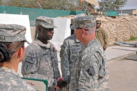 Col. Michael Peterman, 101st Sustainment Brigade commander, shakes hands with Staff Sgt. Kofi Nyarko, 101st Sustainment Brigade Support Operations, after he receives his Bronze Star Medal at the unit's End of Tour Awards Ceremony. (Photo by Sgt. 1st Class Peter Mayes)