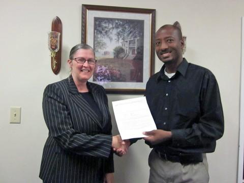 Gladyn Minzey receives the LEAP Organization scholarship from Richard Garrett.
