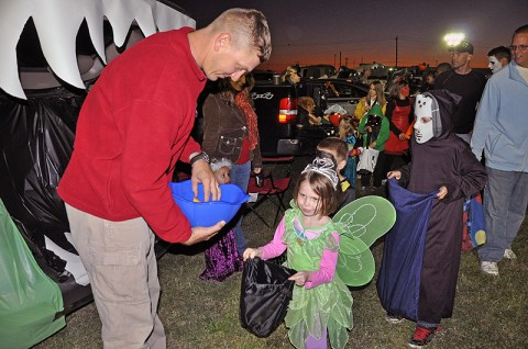 1st Lt. Daniel Collini of Company A, 2nd Brigade Special Troops Battalion, 2nd Brigade Combat Team, 101st Airborne Division (Air Assault), hands out candy to the Strike family members dressed in costumes during the battalion's Trunk or Treat event held at Strike, October 21st.