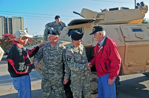 Staff Sgt. Christopher Bill and Spc. Charles Simko, both with Strike's military police from Headquarters and Headquarters Company, 2nd Brigade Special Troops Battalion, 2nd Brigade Combat Team, 101st Airborne Division (Air Assault), shake the hands of World War II Veterans James Chadwell and John Mason next to an M1117 Armored Security Vehicle at Hopkinsville's Veteran's Day Parade, Nov. 5th. Veterans from World War II, Korea, Vietnam, the Middle East and Afghanistan took part in the town's day of honor. (U.S. Army photo by Sgt. Joe Padula, 2nd BCT PAO, 101st Abn. Div.)