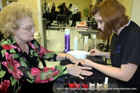 Student Elyse Riley giving Sue Culverhouse her manicure