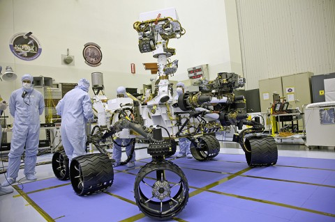 Technicians look over the MSL Curiosity during inspections at the Jet Propulsion Laboratory in Pasadena, CA. (Photo credit: NASA)
