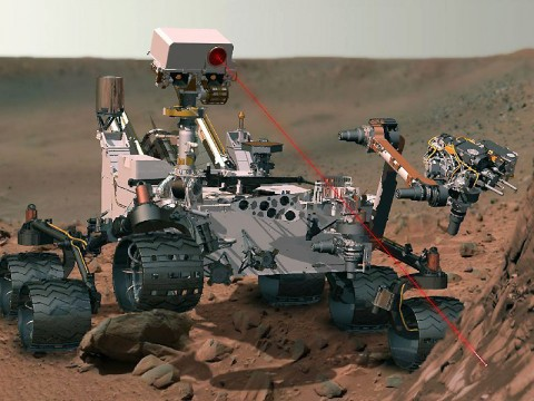 This artist's concept depicts the rover Curiosity, of NASA's Mars Science Laboratory mission, as it uses its Chemistry and Camera (ChemCam) instrument to investigate the composition of a rock surface. ChemCam fires laser pulses at a target and views the resulting spark with a telescope and spectrometers to identify chemical elements. The laser is actually in an invisible infrared wavelength, but is shown here as visible red light for purposes of illustration. (Image Credit: NASA/JPL-Caltech)