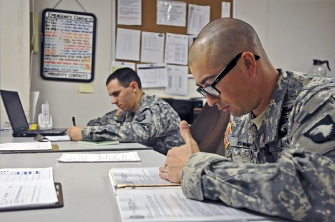Spc. Michael Lombardo, a medic with Headquarters and Headquarters Company, 1st Special Troops Battalion, 1st Brigade Combat Team, 101st Airborne Division, and Sgt. Adam Hawes, a team leader with HHC, 1st STB, check their logs and regulations while on staff duty November 10th. (Photo by Sgt. Richard Daniels Jr.)