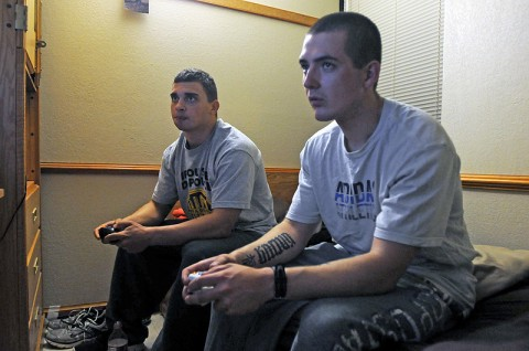 (Left) Spc. Jeremy Sweeting, an assistant gunner with Company B, 2nd Battalion, 327th Infantry Regiment, 1st Brigade Combat Team, and Spc. Sean Russell, a M240 machine gunner, play together on a recently released first-person shooter here at the 1st Brigade barracks Nov. 21st. (Photo by Sgt. Richard Daniels Jr.)