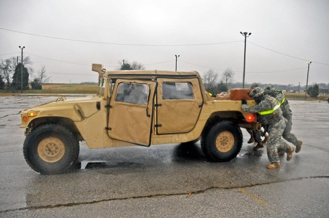 The Strike Soldiers of 1st Battalion, 320th Field Artillery Regiment, 2nd Brigade Combat Team, 101st Airborne Division (Air Assault), push a disabled military vehicle during the 'Top Guns Blitz' at Fort Campbell, KY, Dec. 7th. Soldiers had to push the vehicle about 50-meters to complete this portion of the event. (U.S. Army Photo By Spc. Shawn Denham, PAO, 2nd BCT, 101st Abn. Div.)
