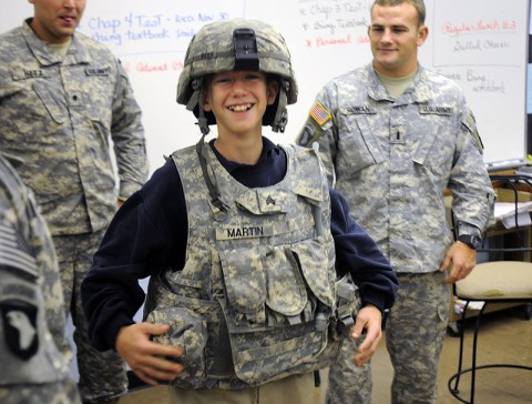 Jonah Gelhaust, a 6th grader at Saint Edwards School here, laughs while trying on the body armor and helmet of one of the soldiers from 2nd Battalion, 320th Field Artillery, 1st Brigade Combat Team Nov. 29th. The soldiers visited the school in order to build a relationship with it and the kids. (Photo by Sgt. Jon Heinrich)