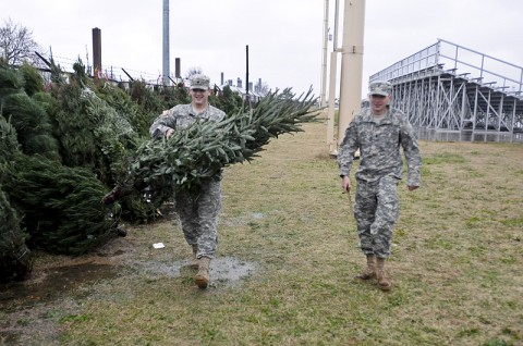 Spc. William Snyder, a gunner with Headquarters and Headquarters Company, 1st Battalion, 327th Infantry Regiment, carries a Christmas tree for Spc. Joshua Hulburt, a mortar man with HHC, 1-327th Inf. Bn, donated by Trees for Troops here at the Fryar Stadium Dec. 5th. (Photo by Sgt. Richard Daniels Jr)