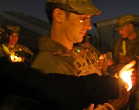 Capt. Paul Rickmeyer, the 159th Combat Aviation Brigade intelligence officer, carefully holds his candle while another soldier from the deployed unit at Kandahar Airfield uses it to light their's during a Christmas Eve service. (Photo by Sgt. 1st Class Stephanie Carl, 159th CAB)