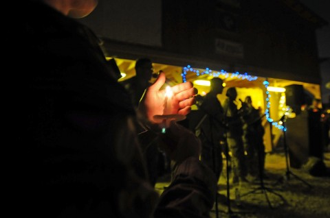 Staff Sgt. Joey Honeycutt, the 159th Combat Aviation Brigade's chaplain assistant NCO in charge, holds a candle while a band plays during a Christmas Eve service on Mustang Ramp at Kandahar Airfield, Afghanistan. (Photo by Sgt. 1st Class Stephanie Carl, 159th CAB)