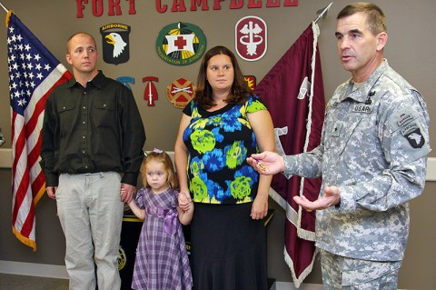 Retired Sgt. Cory Perrin, his wife Nancy and their daughter Sumer listen as Brig. Gen. Jeffrey Colt 101st Airborne Division (Air Assault) Deputy Commanding General for Support explains the history and honor behind the Purple Heart medal before presenting one to Perrin Dec. 15th at the Fort Campbell Warrior Transition Battalion.