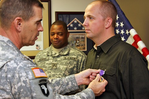101st Airborne Division (Air Assault) Deputy Commanding General for Support Brig. Gen. Jeffrey Colt pins a Purple Heart medal on Retired Sgt. Cory Perrin Dec. 15th at the Fort Campbell Warrior Transition Battalion.