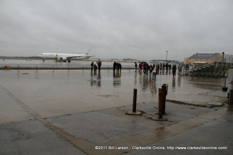 Family members wait in the rain for their loved ones to disembark from the aircraft.